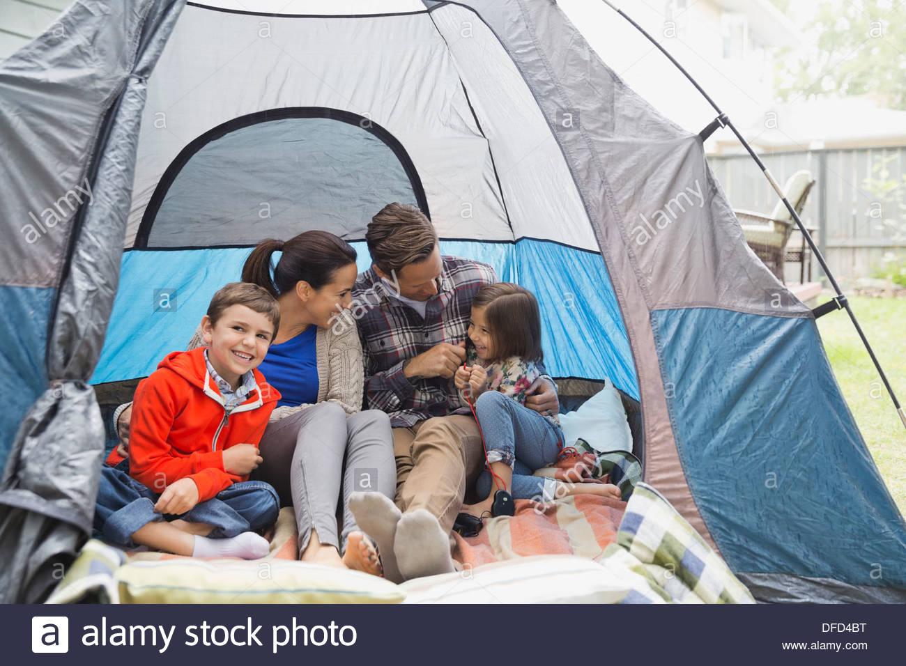 Vierköpfige Familie sitzen zusammen im Zelt Stockbild