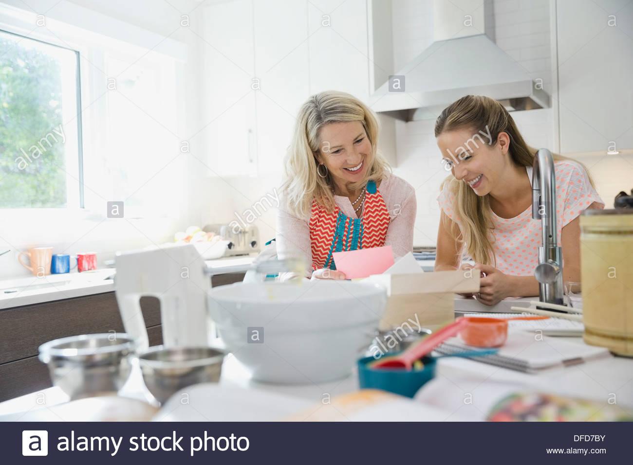 Glückliche Mutter und Tochter lesen Rezepte in der Küche Stockbild