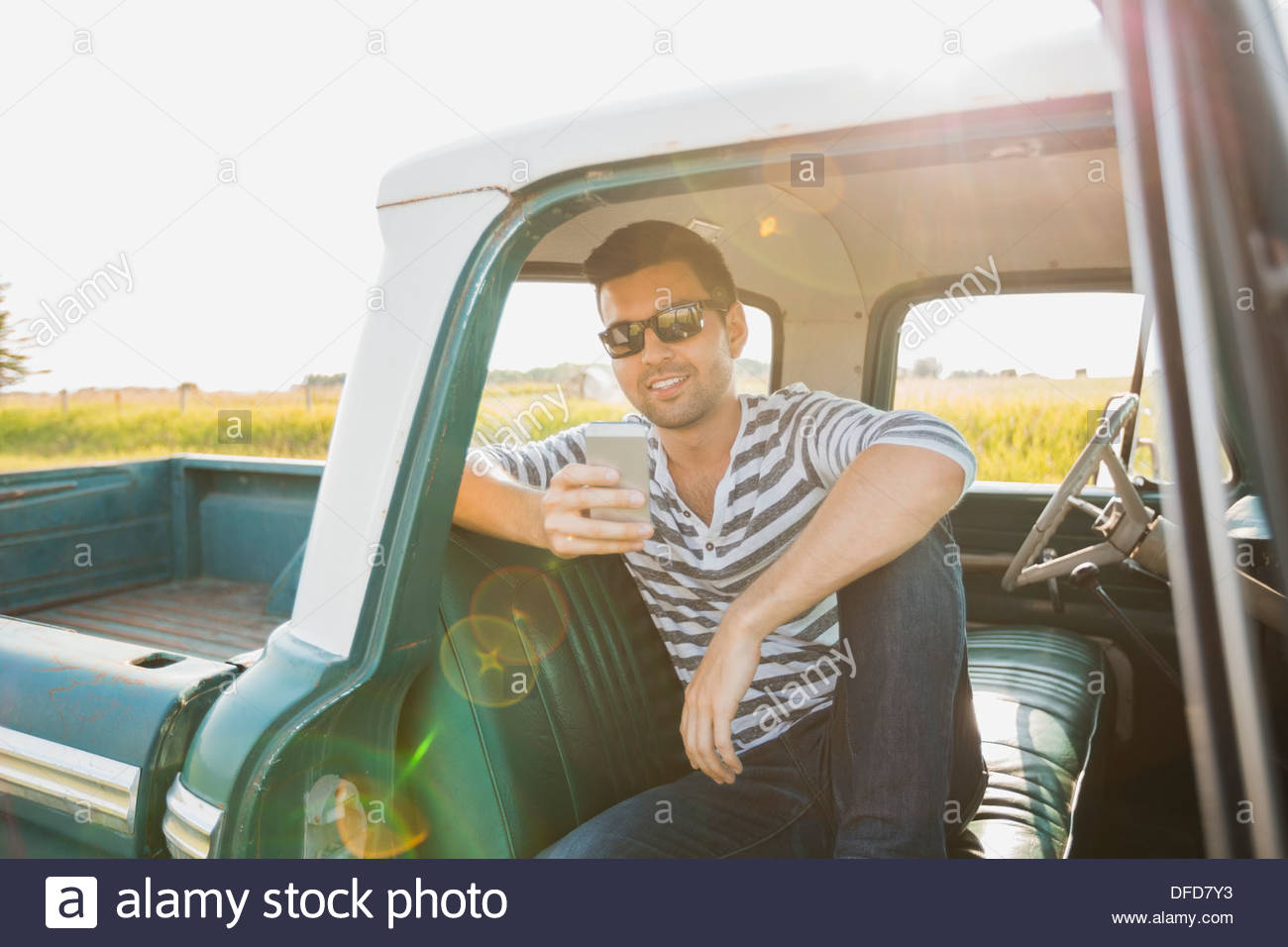 Junger Mann, Blick auf Smartphone in Pick-up-truck Stockbild