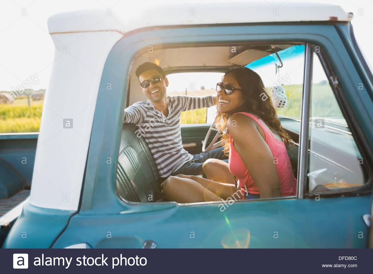 Fröhliches junges Paar sitzt in Pick-up-truck Stockbild