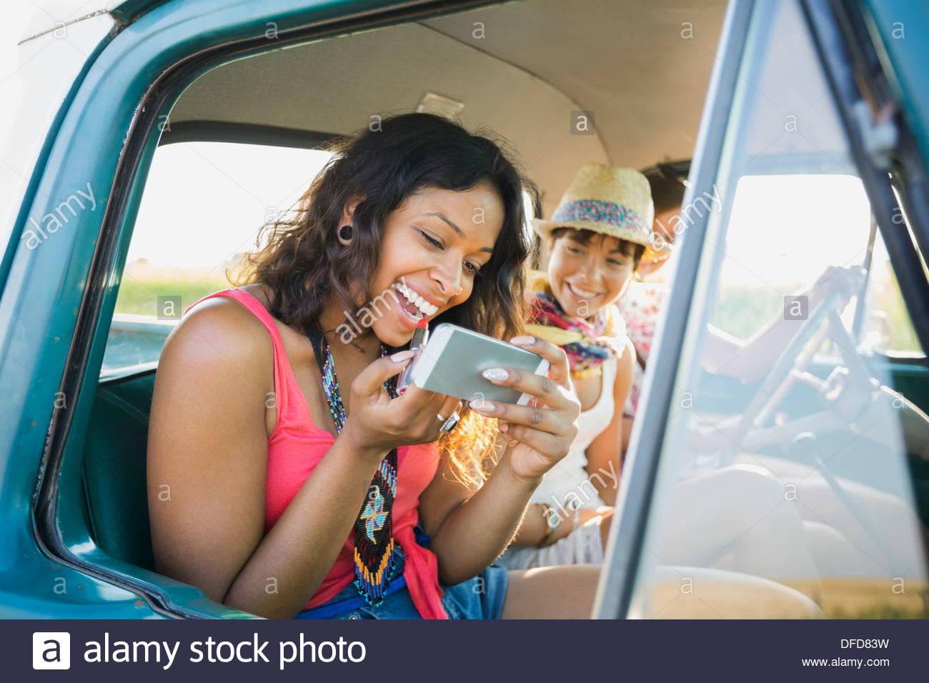 Frau Auftragen von Lippenstift mit Handy in Pick-up-truck Stockbild