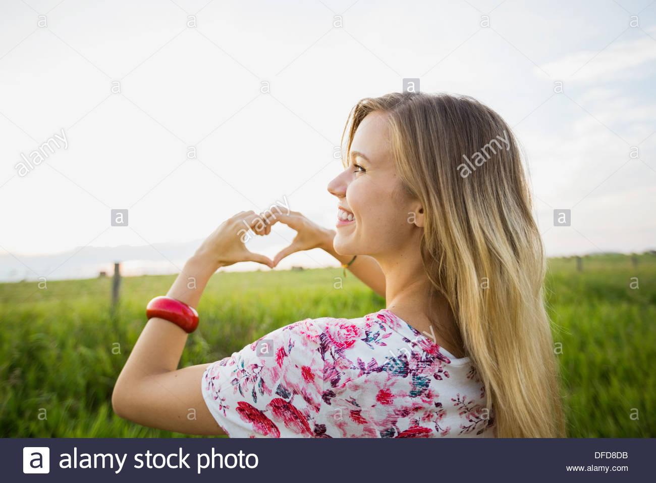 Über die Schulter-Blick der jungen Frau macht Herzform mit Händen Stockbild