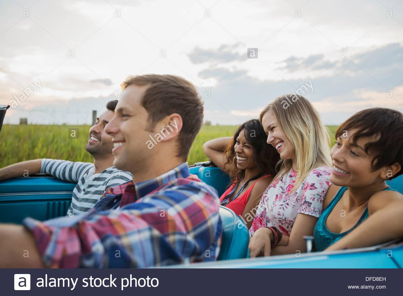 Fröhliche Freunde sitzen im Cabrio Stockbild
