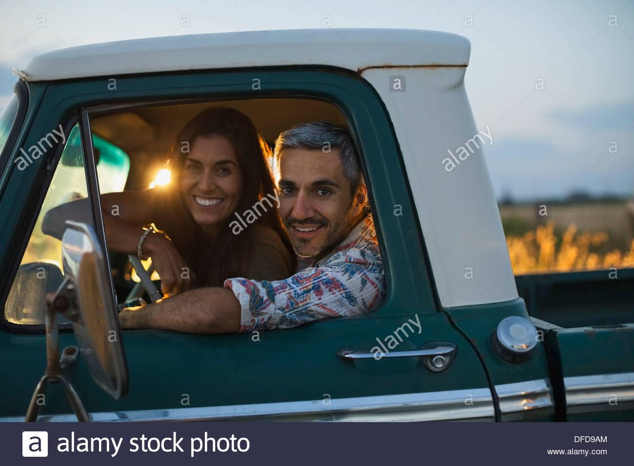 Fröhliches paar sitzt in Pick-up-truck Stockbild