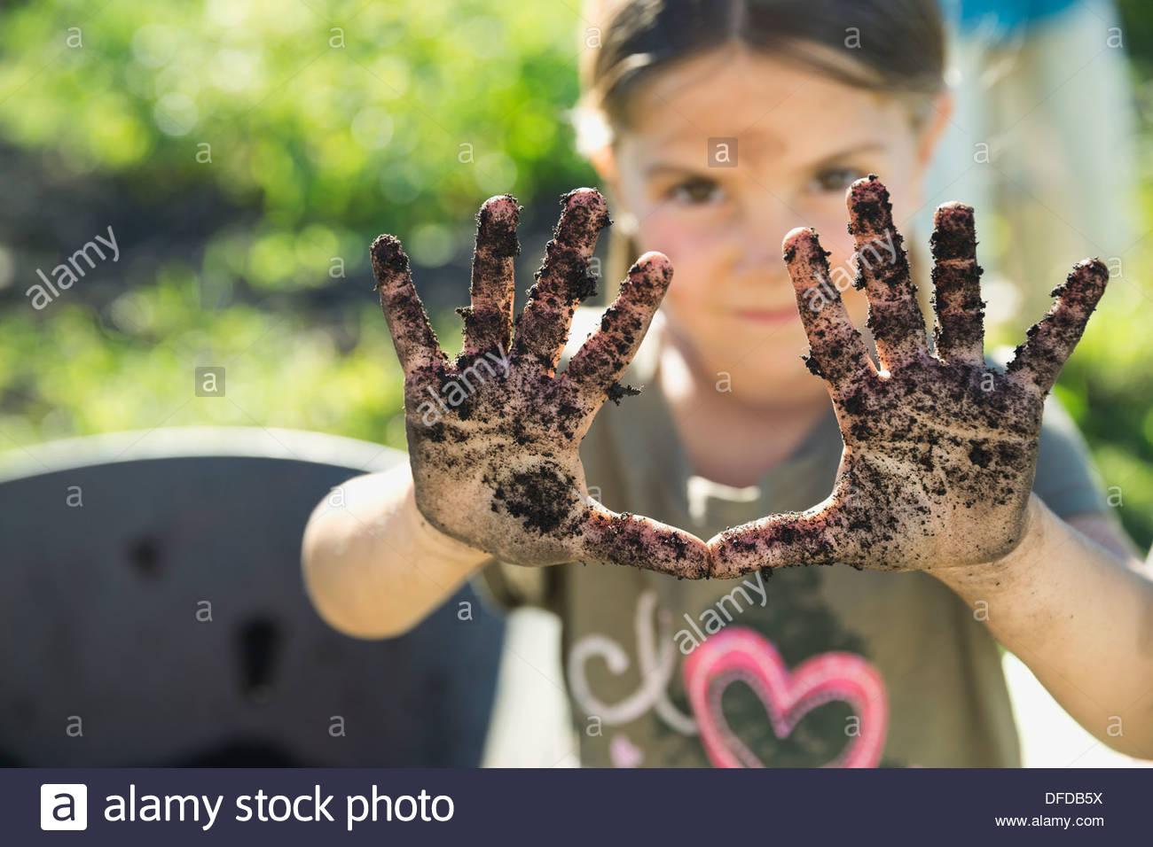 Kleines Mädchen zeigt Hände voller Garten Schmutz Stockbild