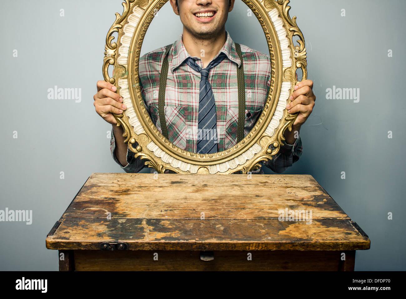Junger Mann, Blick durch einen leeren Bilderrahmen Stockfoto, Bild ...