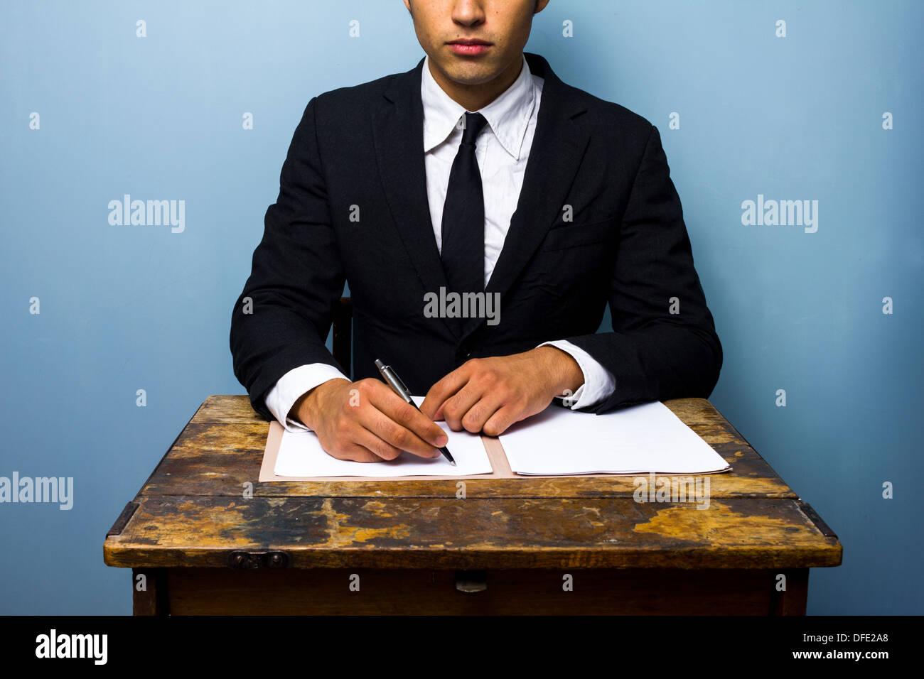 Junger Geschäftsmann sitzt auf einem alten Schreibtisch und Vertragsabschluss Stockbild