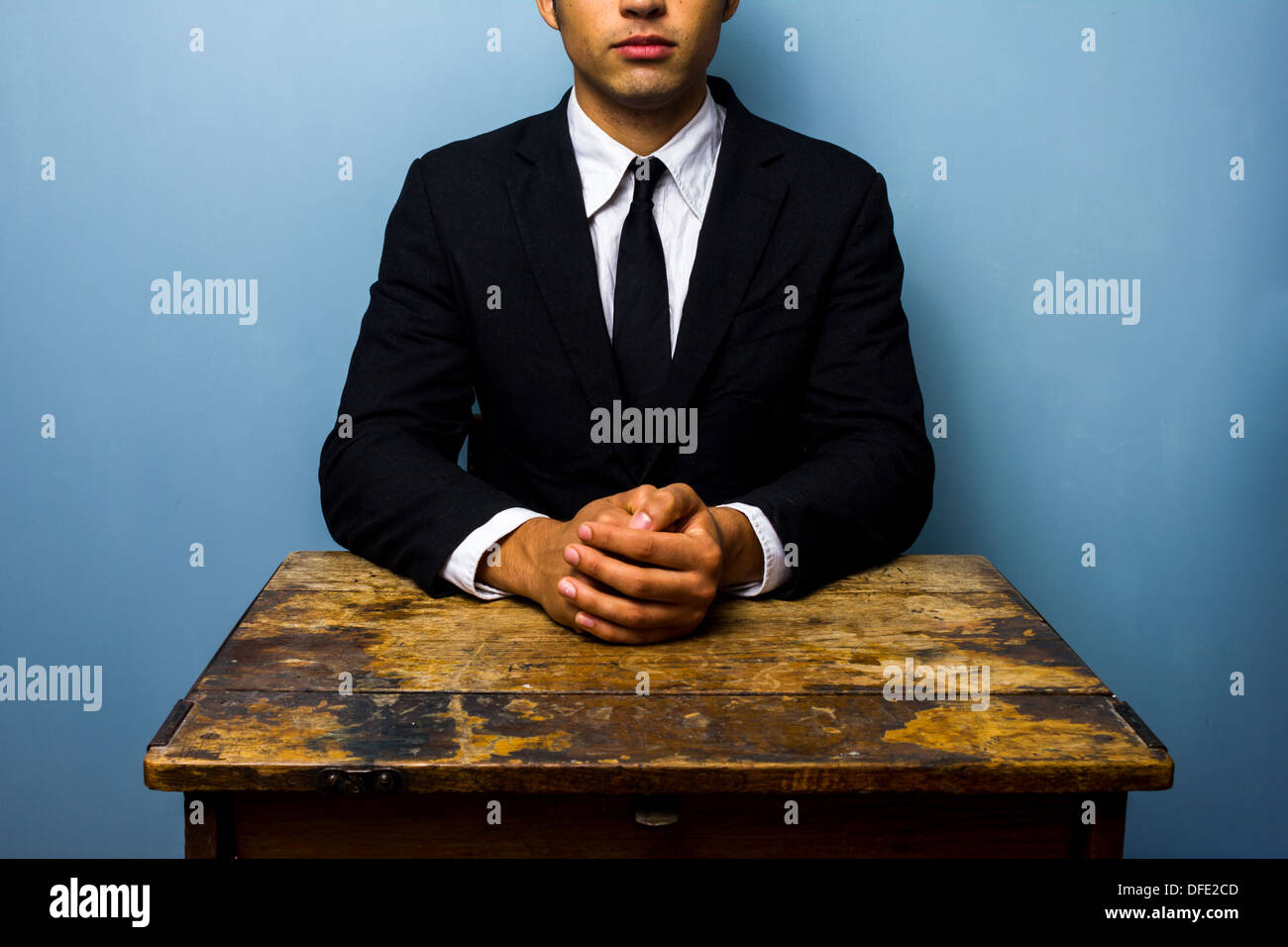 Junger Geschäftsmann sitzt an einem alten Schreibtisch mit seinen Händen gefaltet Stockbild
