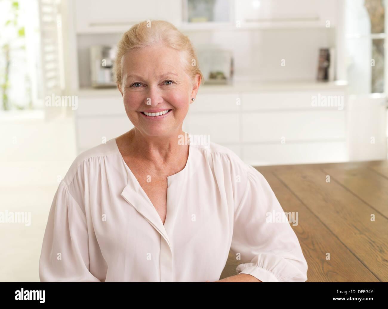 Ältere Frau lächelnd in Küche Stockbild