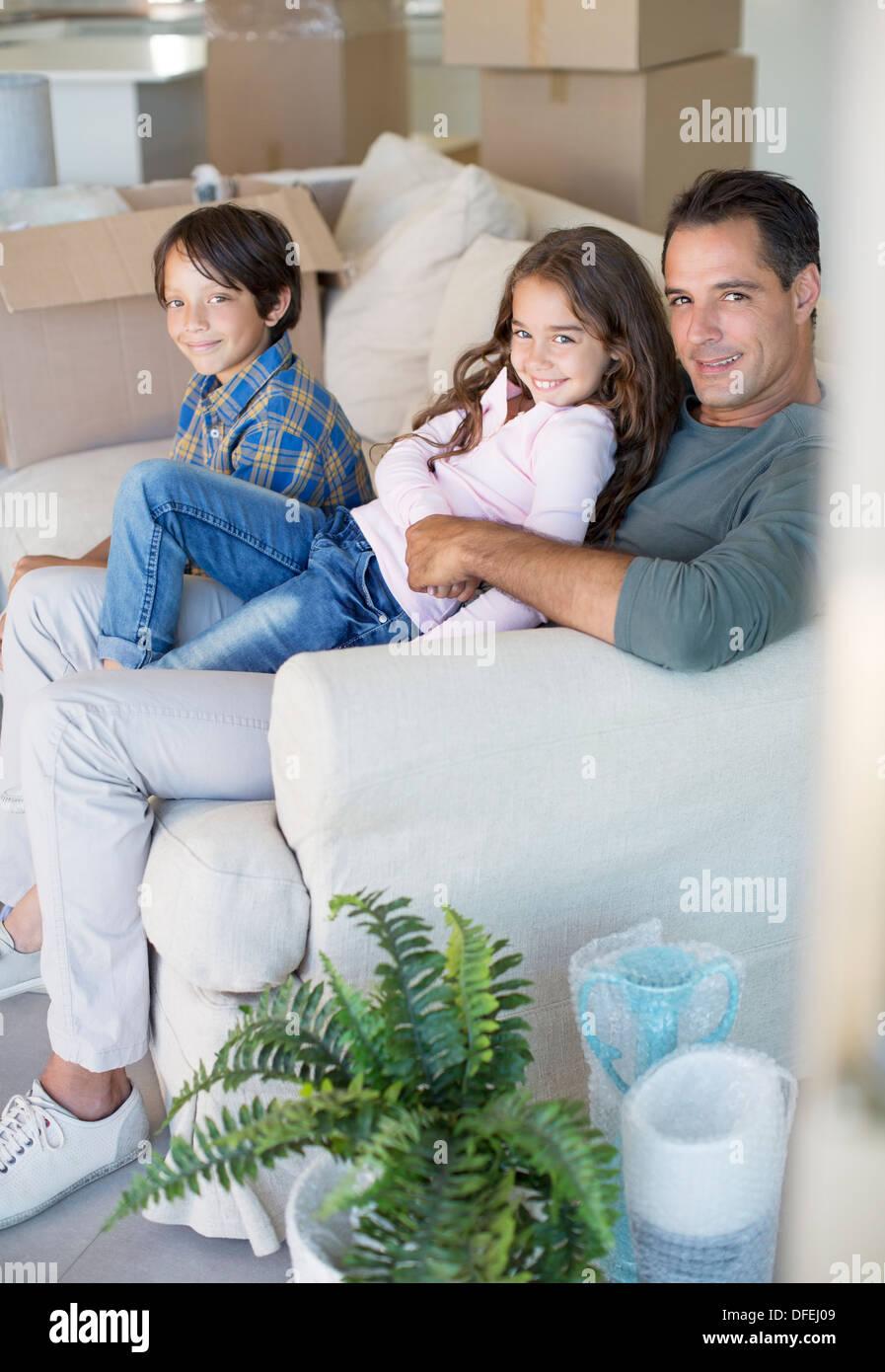 Vater und Kinder entspannend auf Sofa unter Kartons Stockfoto