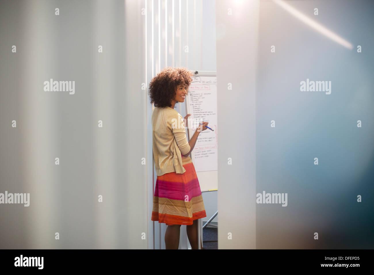 Geschäftsfrau am Whiteboard im Konferenzraum Stockbild
