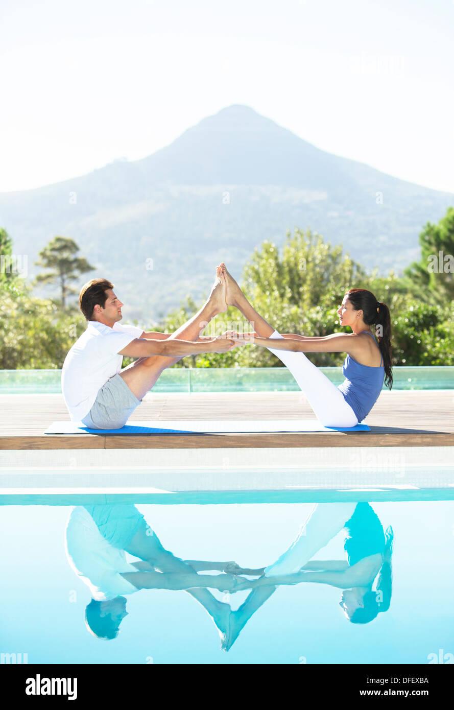 Paar üben Yoga am Pool Stockfoto