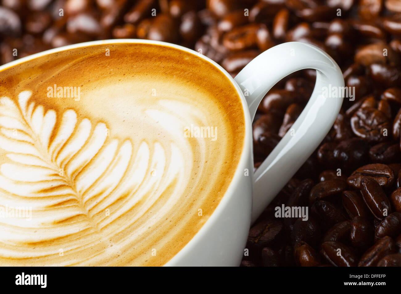 Latte Art, Coffee in Kaffeebohnen Hintergrund Stockfoto