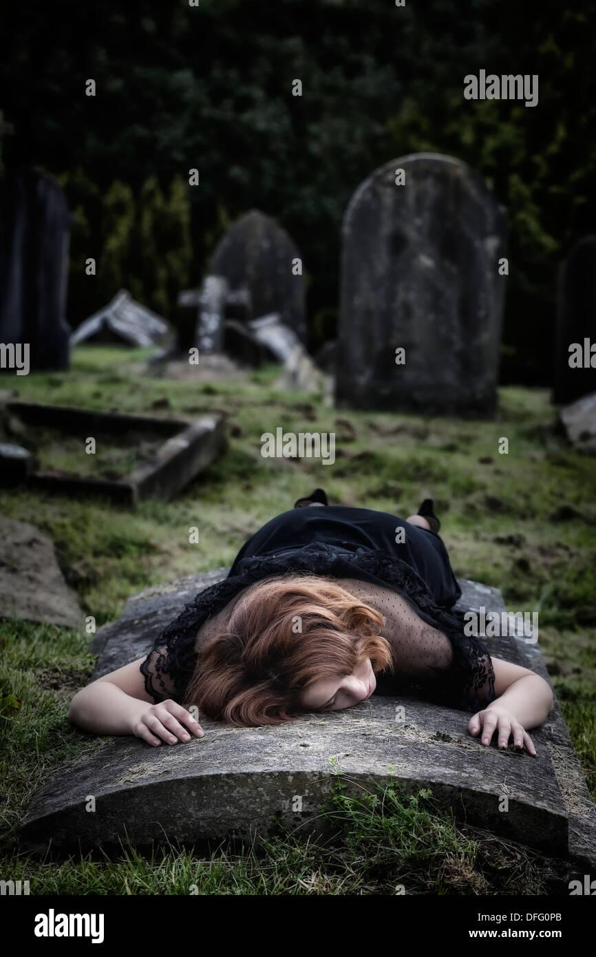 eine Frau liegt auf einem Grab Stockbild