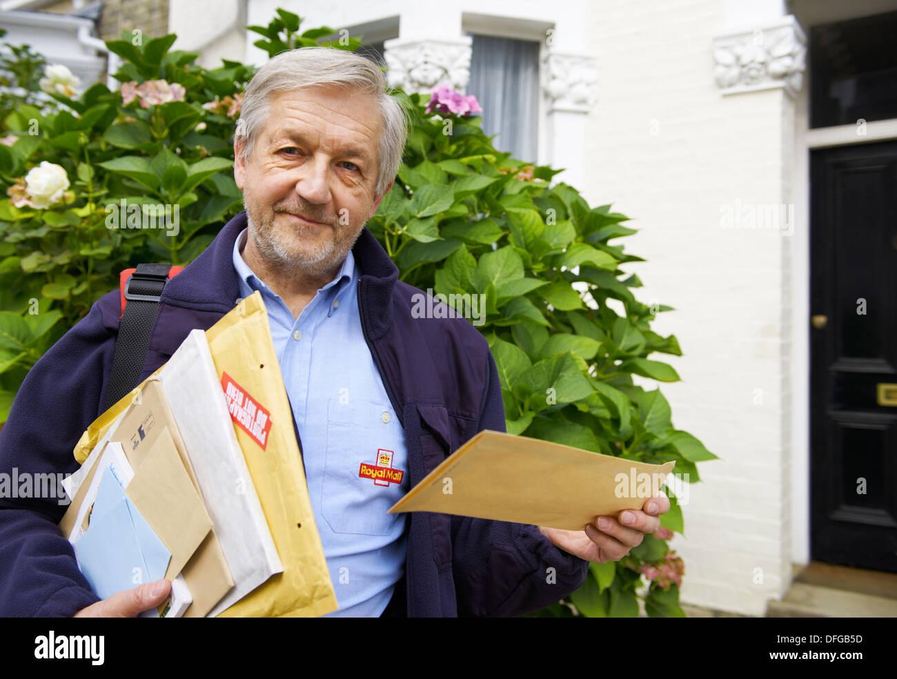 Royal Mail Postbote liefert regelmäßig Briefe, Luftpost, Päckchen und Pakete im Wohngebiet im Vereinigten Königreich Stockbild