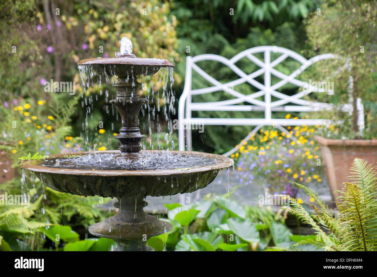 Wasser-Brunnen und weiß verzierten Metallbank Lost Gardens of Heligan, Cornwall, UK Stockbild