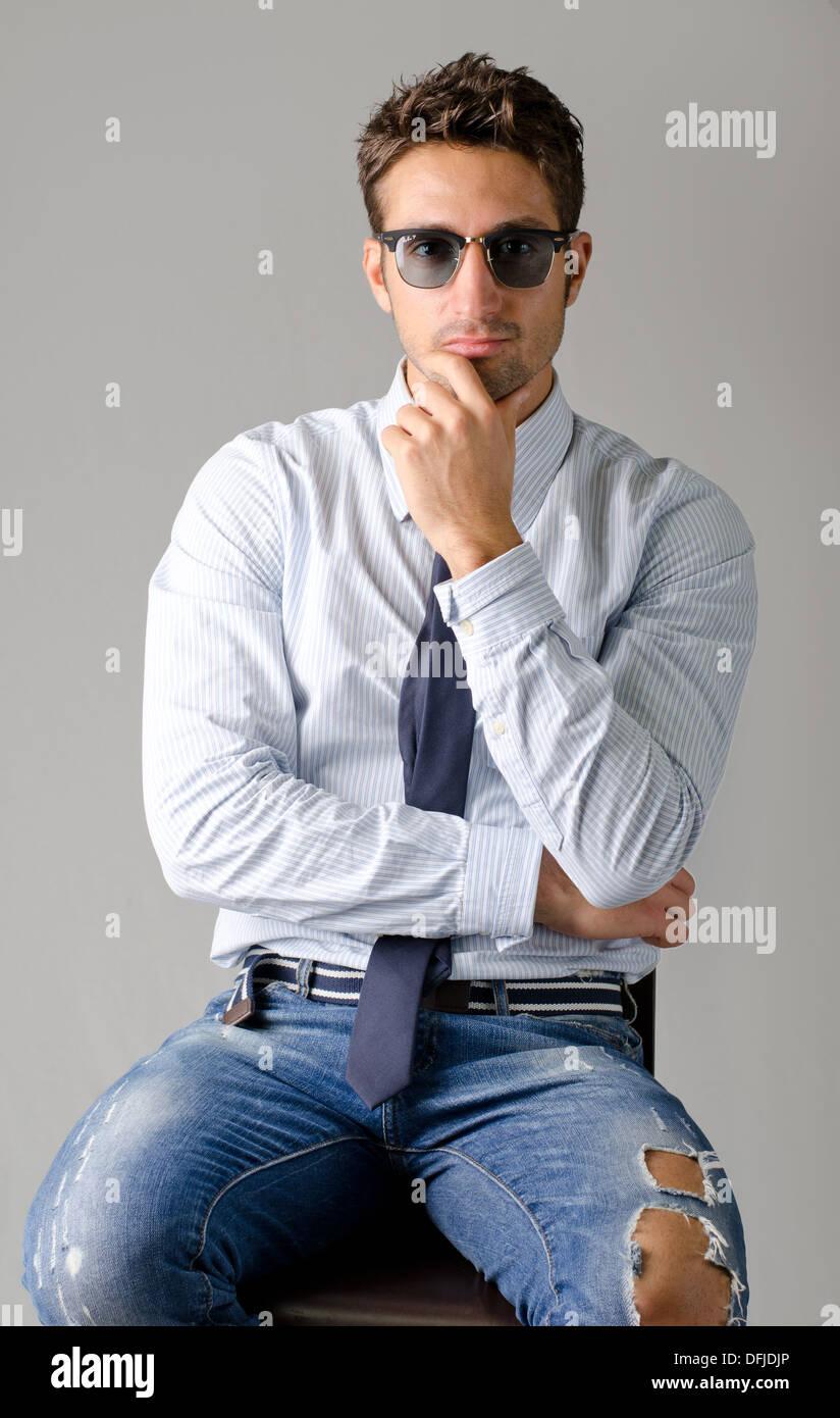 Hübscher junger Mann in Hemd, Krawatte und zerrissene Jeans, sitzend, isoliert auf grauem Hintergrund Stockbild