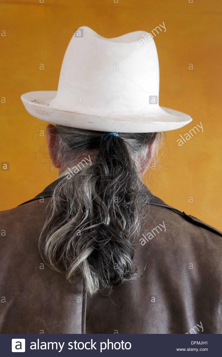 Mann mit Pferdeschwanz trägt einen weißen Putz Fedora Hut Stockbild