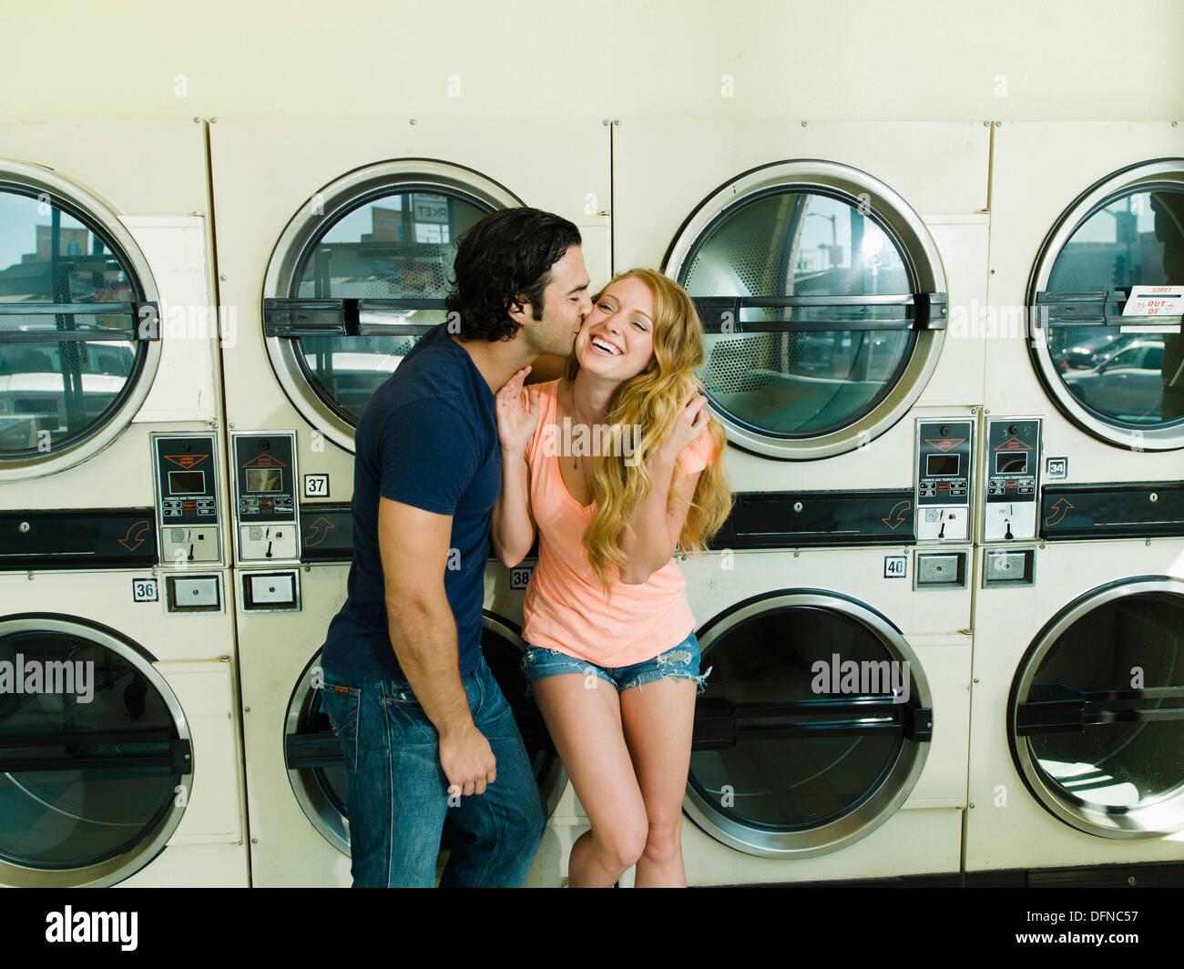 Ein junger Mann küsst das Küken von einer hübschen Frau in San Diego Münze Waschsalon. Stockbild