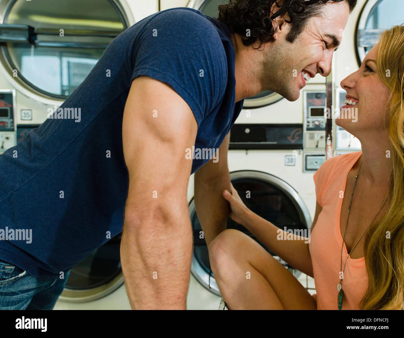 Ein kluger junger Mann ruft in San Diego Münze Waschsalon gemütlich zu einer schönen Frau. Stockbild