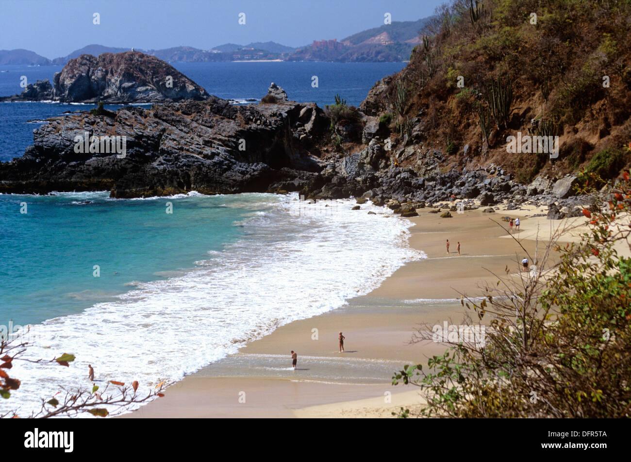 Playa Vista Hermosa, erstreckt sich zwischen natürlichen Felsformationen und Las Brisas Hotel, Ixtapa/Zihuatanejo, Mexiko. Stockbild