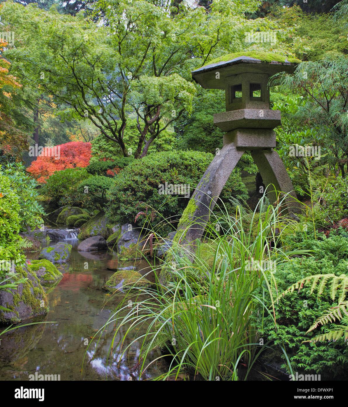 Japanische Steinlaterne im Garten mit Steinen Bäume Pflanzen und ...