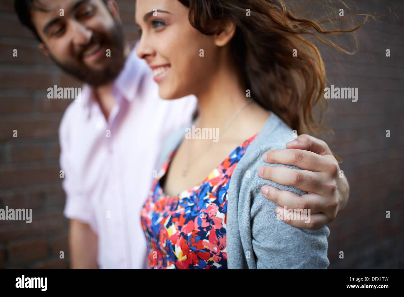 Gut aussehender Mann umfassenden junges Mädchen beim gehen im freien Stockbild