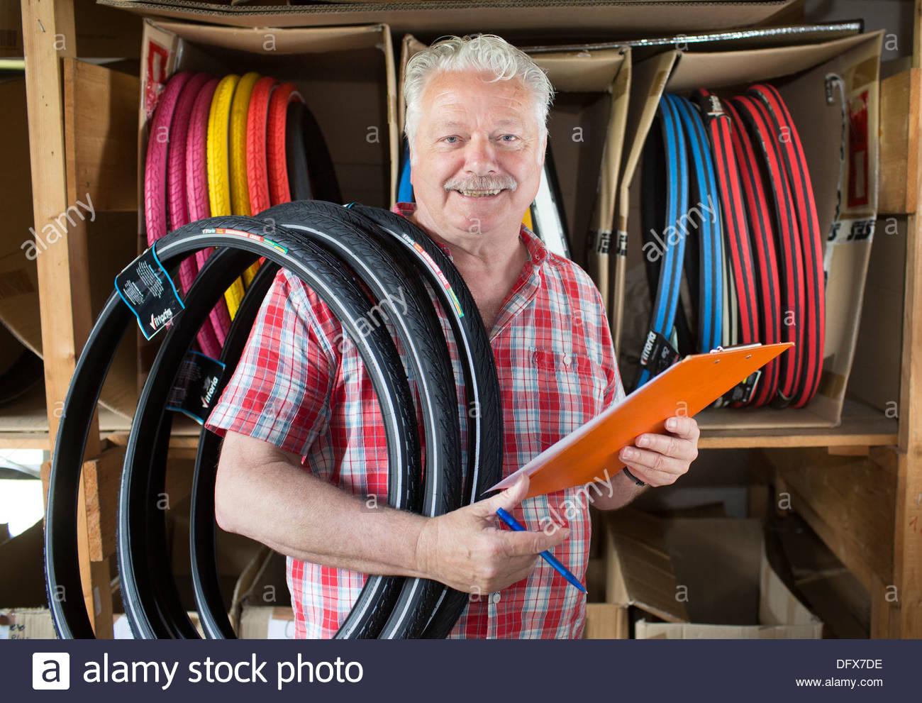 Alter Mann arbeitet in einem Reifenshop Stockbild