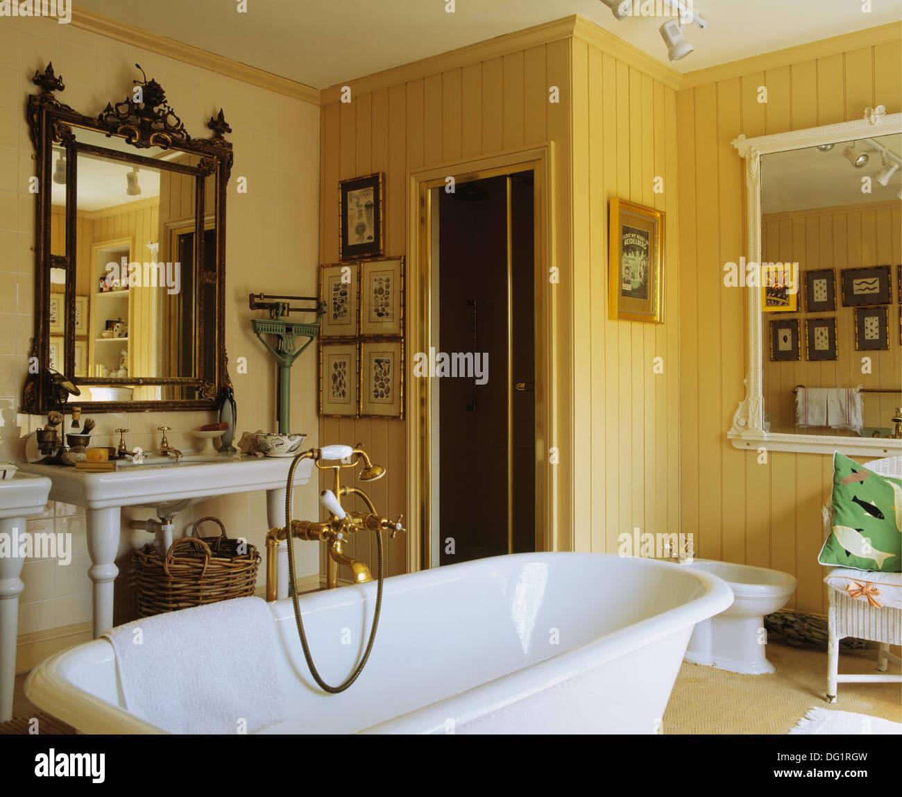 Antiker Spiegel über dem Waschbecken im gelben Badezimmer mit ...