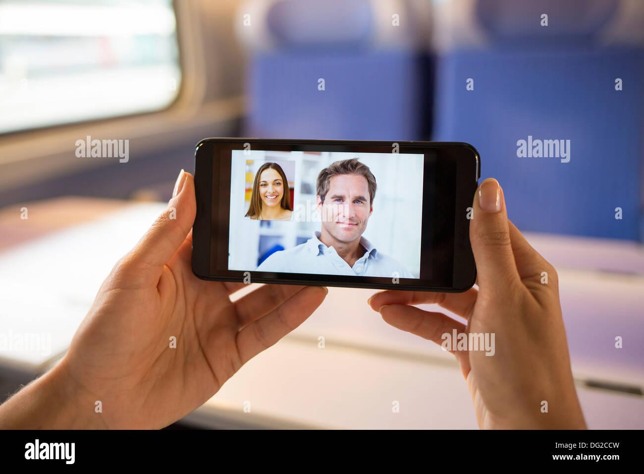Frau in Bahn im Chat auf ihrem Handy. Video-Konferenz Stockbild