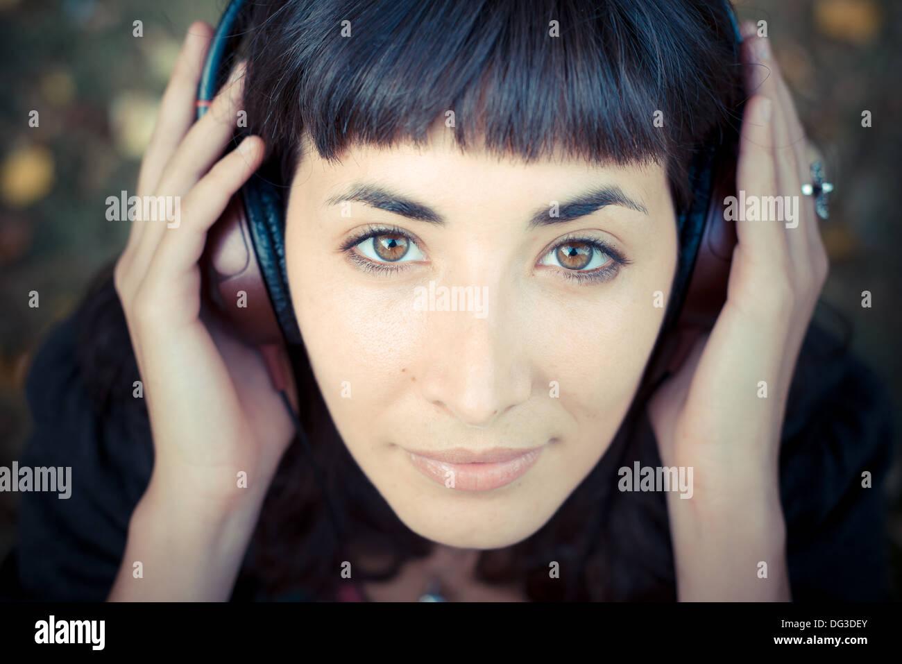 junge schöne Frau anhören von Musik im Park im Herbst Stockbild