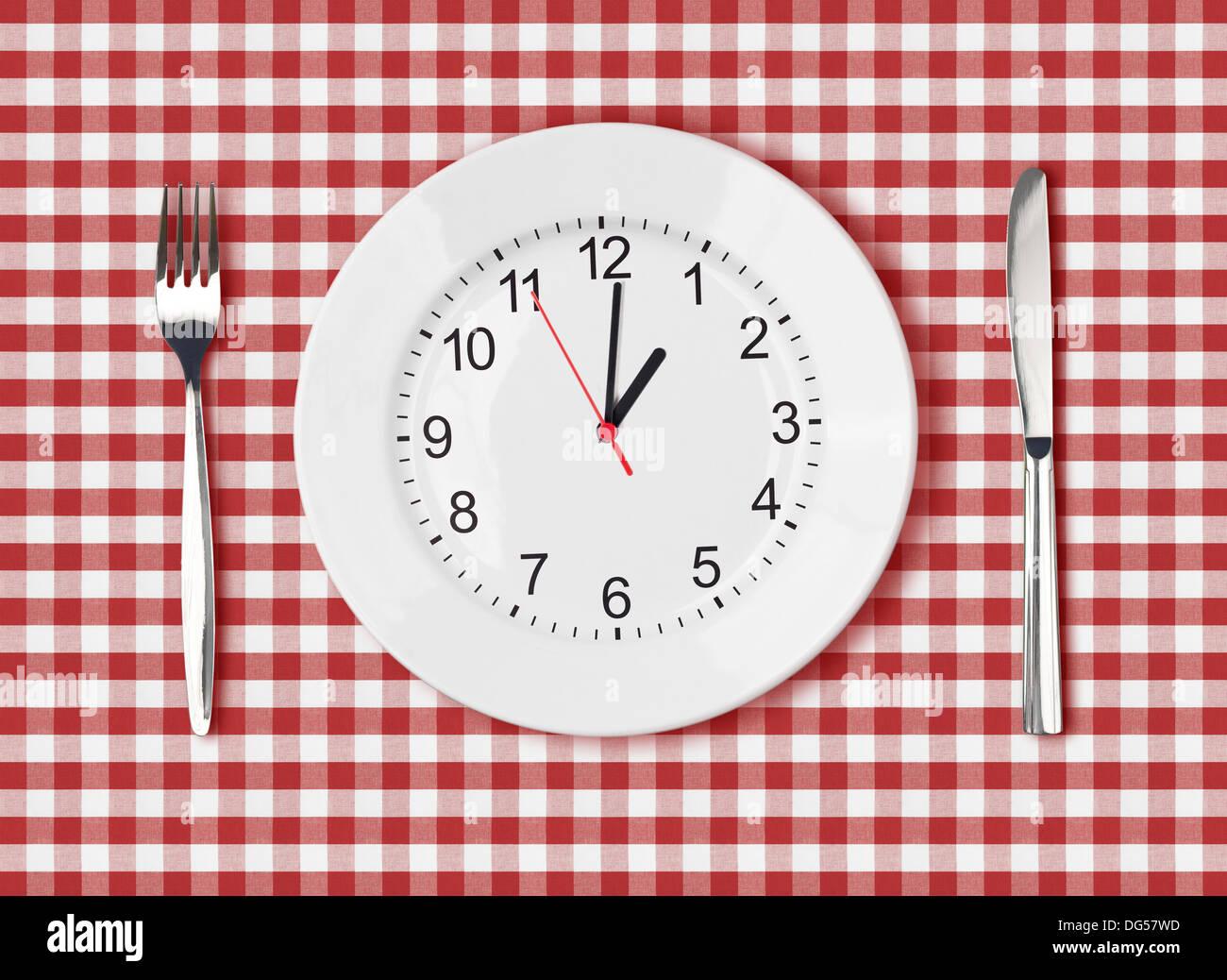 Messer, weiße Platte mit Ziffernblatt und Gabel auf roten Picknick Tischdecke Stockbild