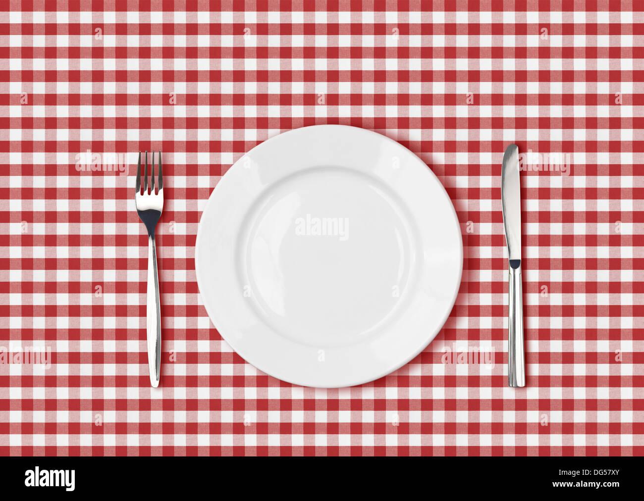 Messer, weißen Teller und Gabel auf roten Picknick Tischdecke Stockbild