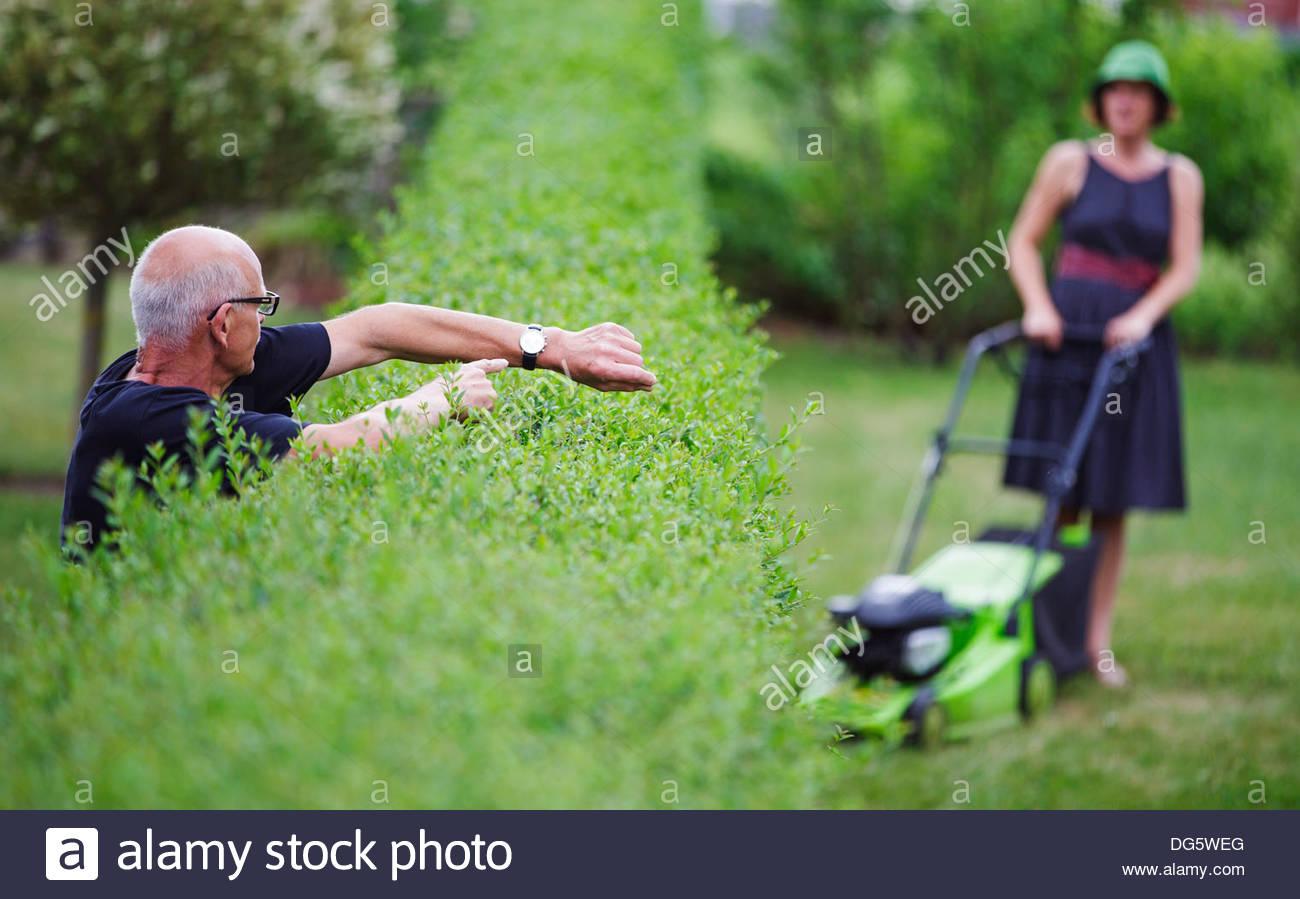 Senior woman zeigt Zeit, eine Frau mit Rasenmäher Stockbild