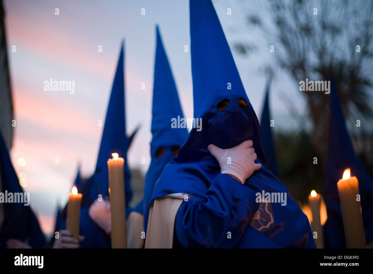 Mit Kapuze Büßer mit Kerzen in der Abenddämmerung, Karwoche, Sevilla, Spanien Stockfoto
