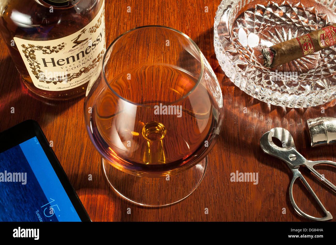 Schnaps und Zigarren - ein Cognac-Schwenker Glas Hennessy Cognac mit einem Teil geraucht, Zigarre in den Aschenbecher Stockbild