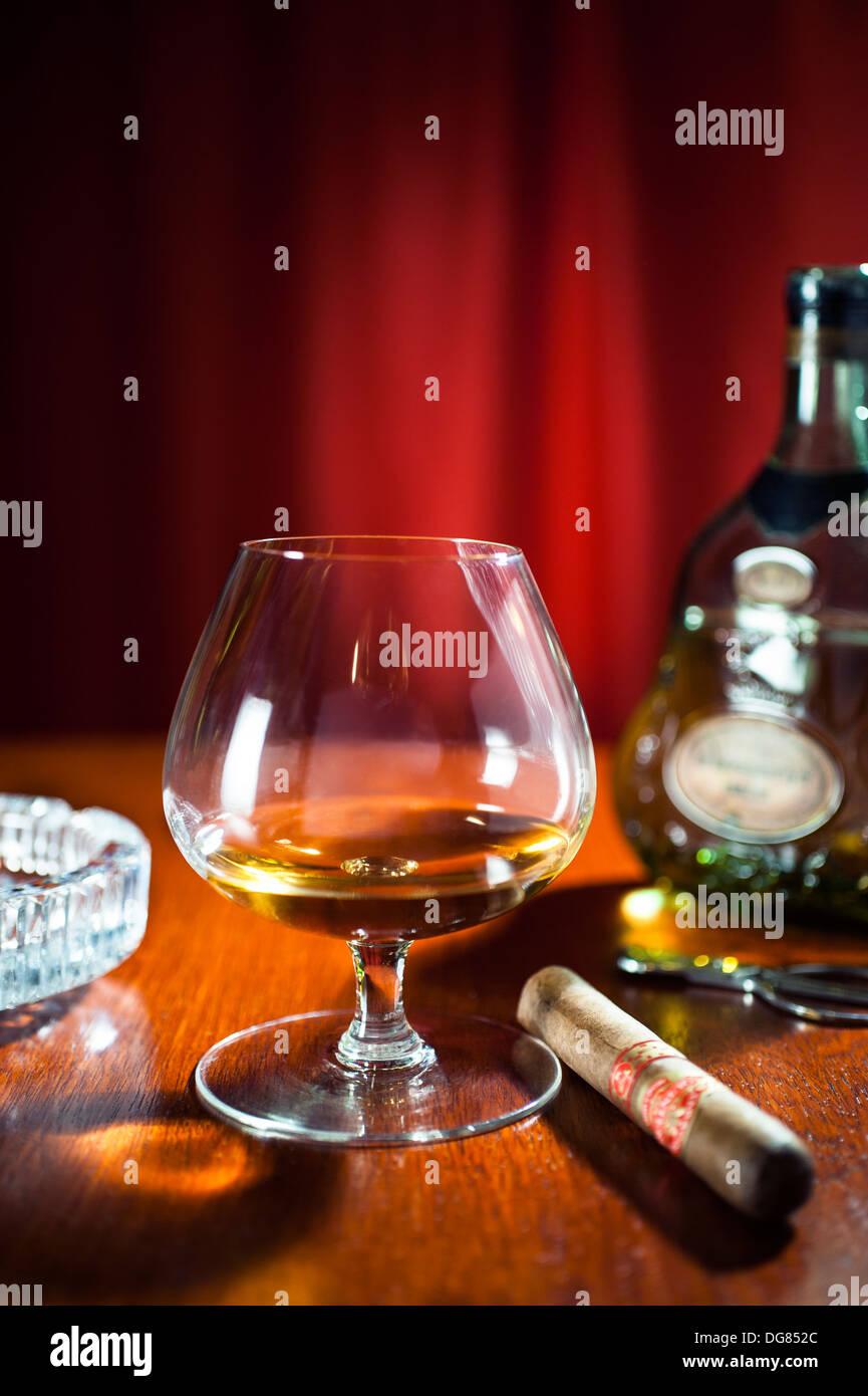 Schnaps und Zigarren - ein Cognac-Schwenker Glas Hennessy XO Cognac mit einer großen Zigarre Stockbild