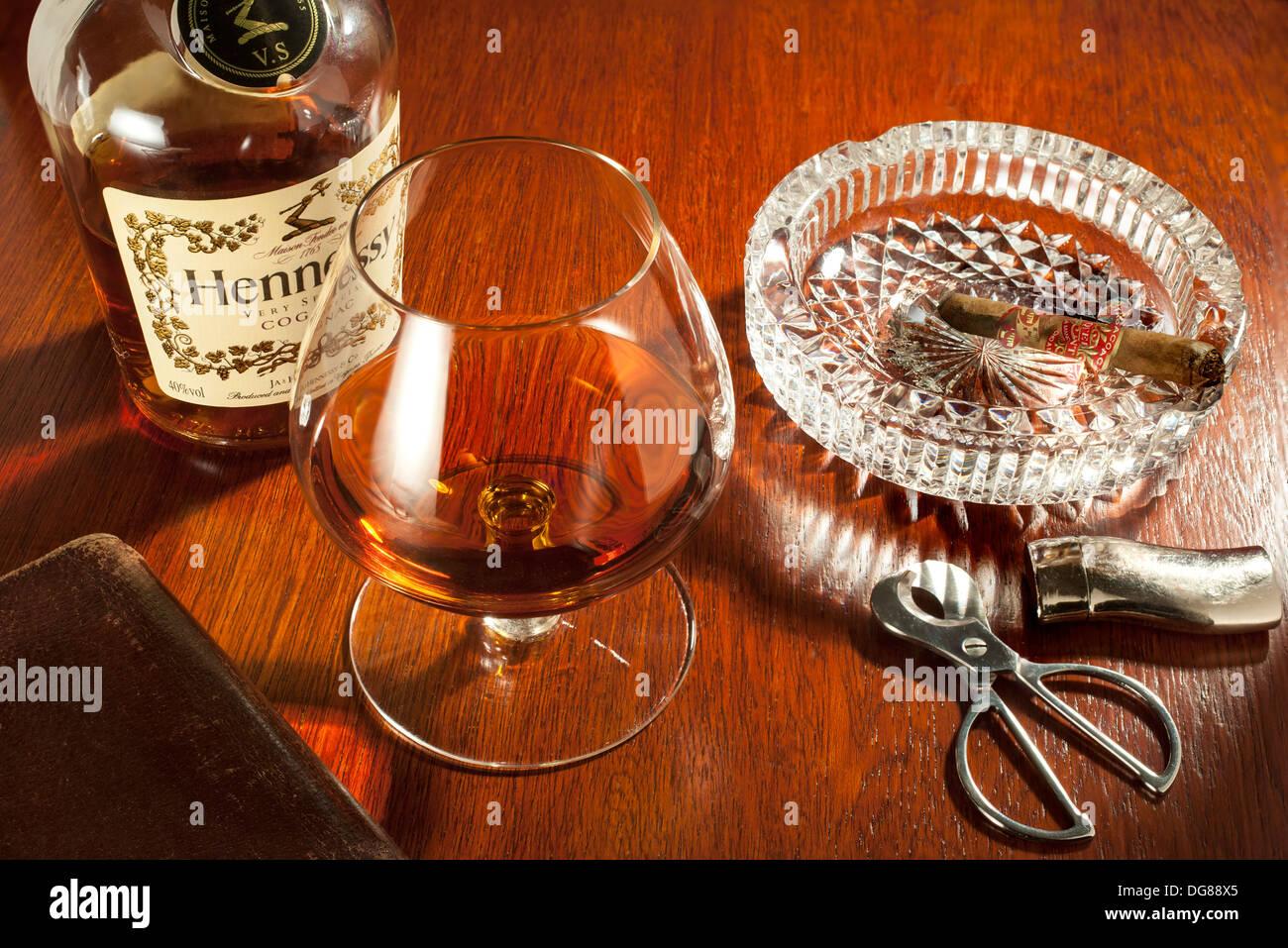 Schnaps und Zigarren - ein Cognac-Schwenker Glas Hennessy Cognac mit einem Teil rauchte Zigarre im Aschenbecher Stockbild
