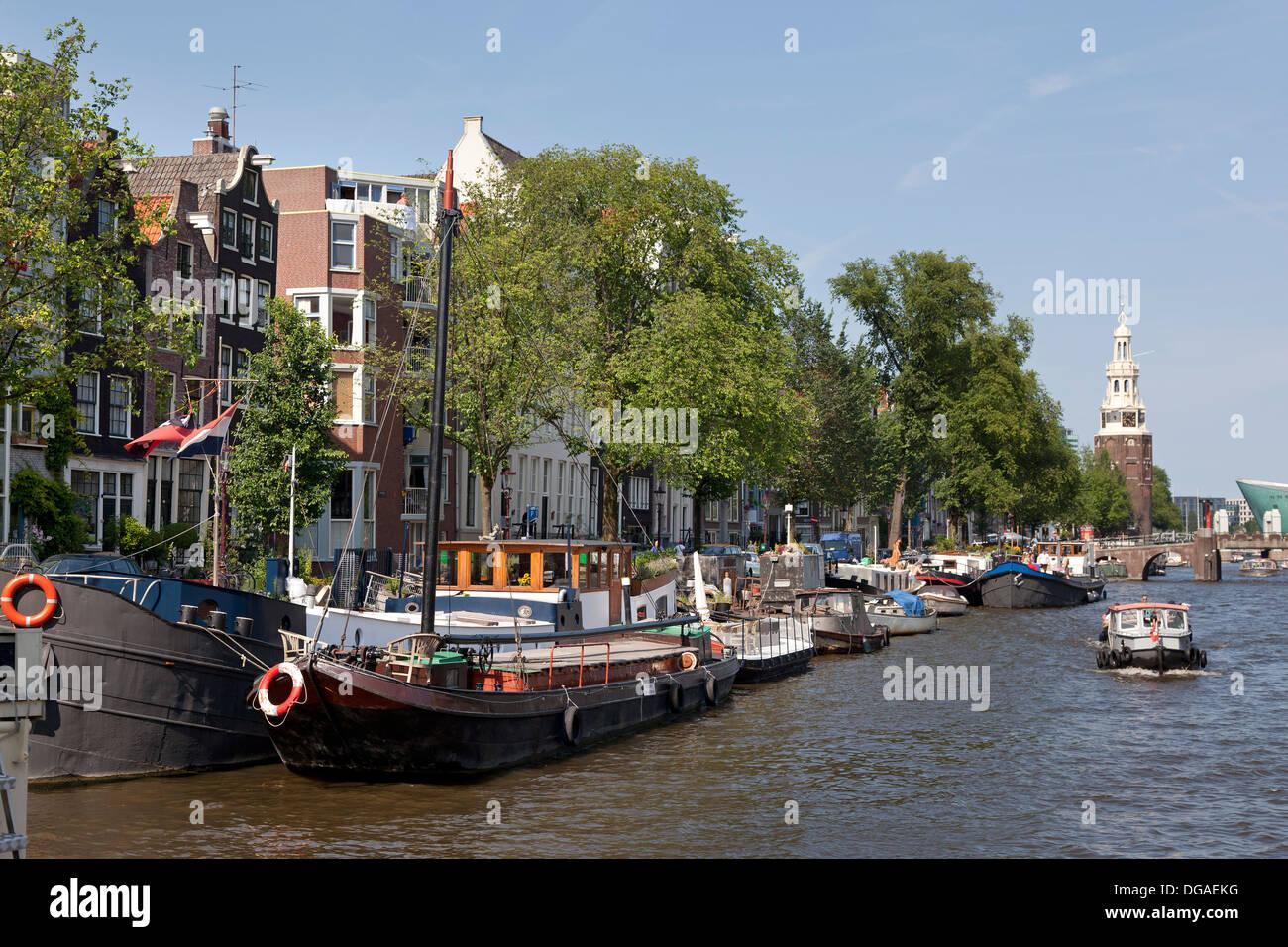 Schiffe im Kanal von Amsterdam mit im Hintergrund der Montalbaan-Turm Stockbild
