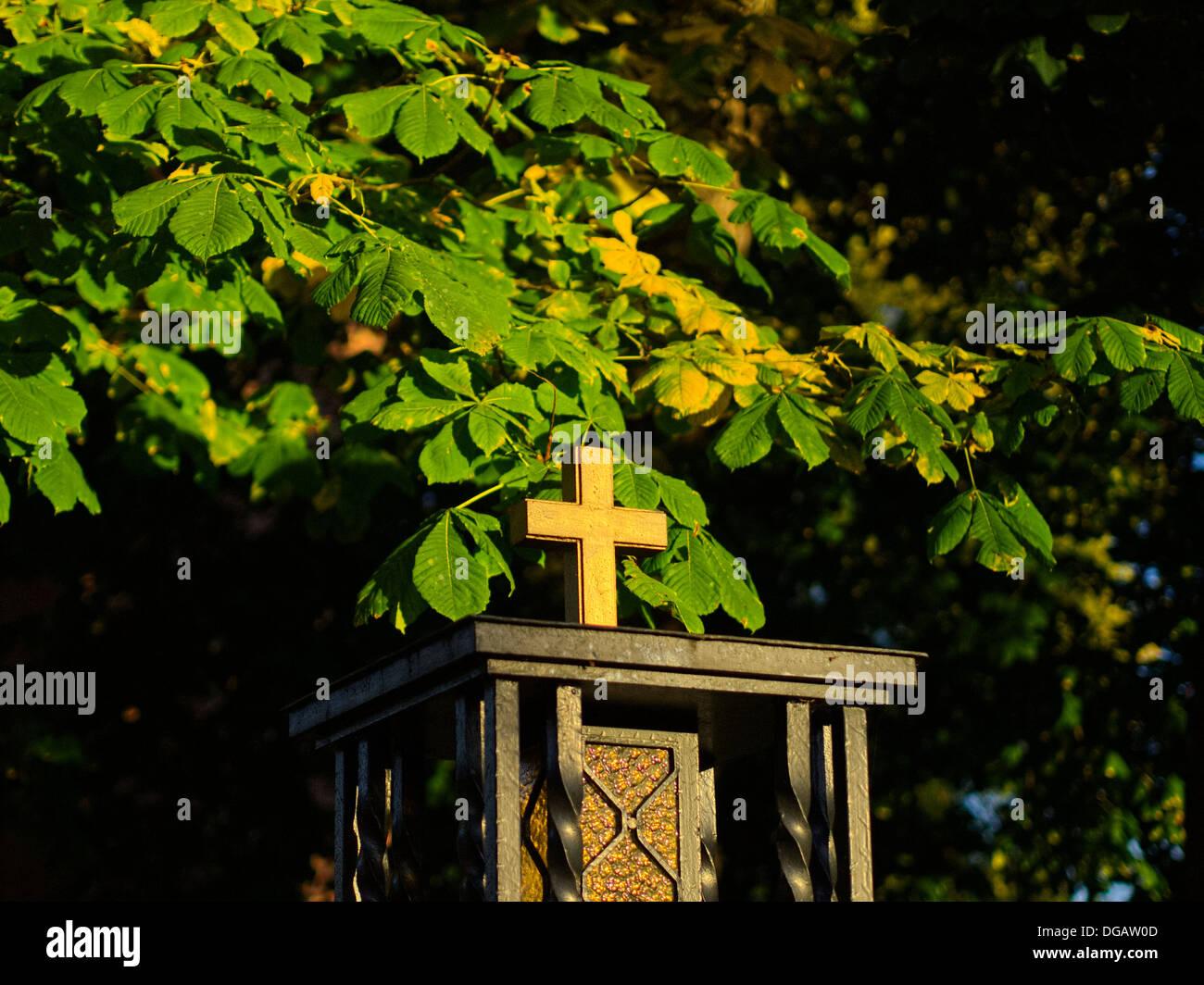 Kreuz, strahlt in der Abendsonne, herbstliche Laub Stockbild