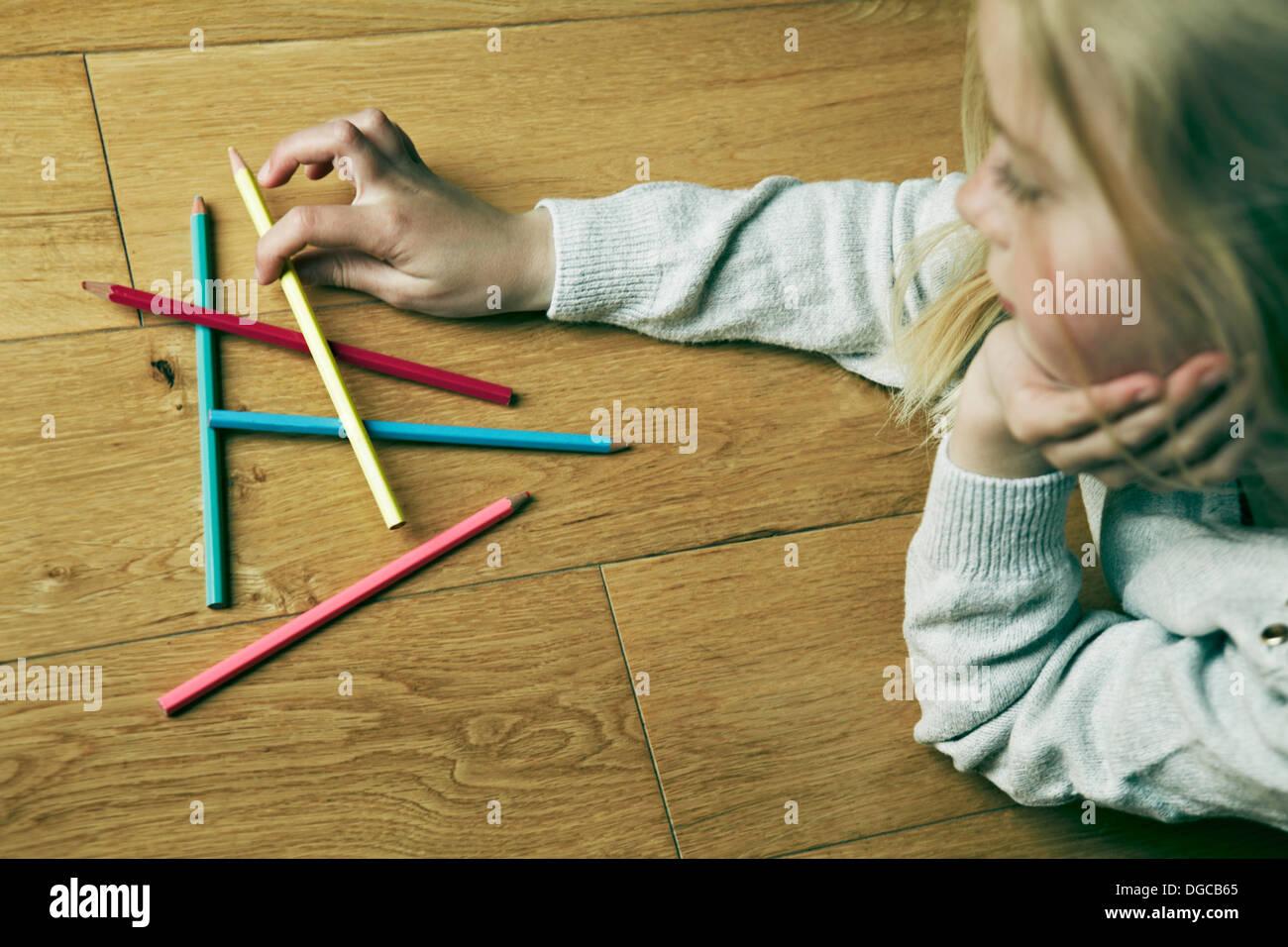 Junges Mädchen auf Boden betrachten Buntstifte Stockbild