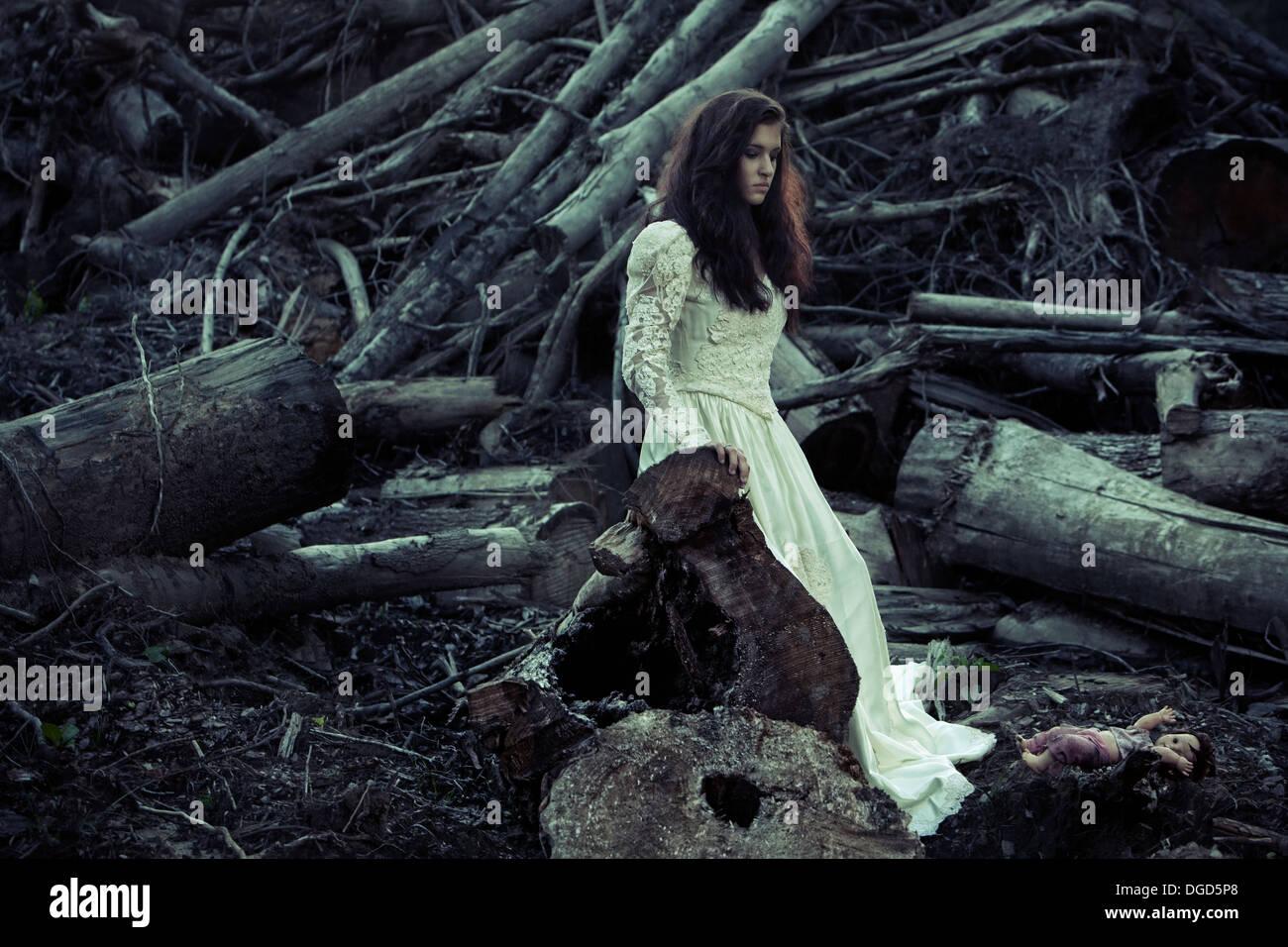 Frau in antiken Brautkleid vor abgespeckte Bäume und gruselige Puppe Stockbild