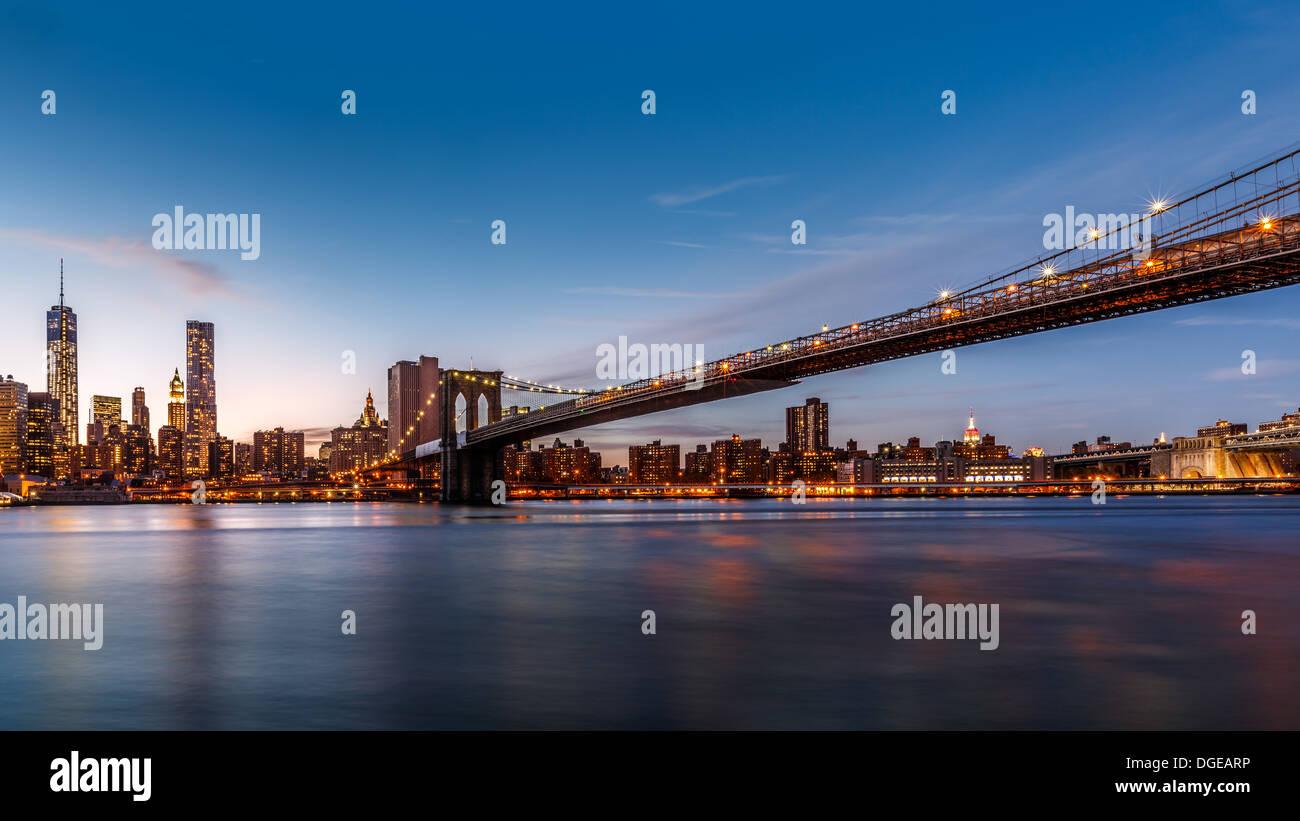 Brooklyn Bridge über den East River in der Abenddämmerung Stockbild