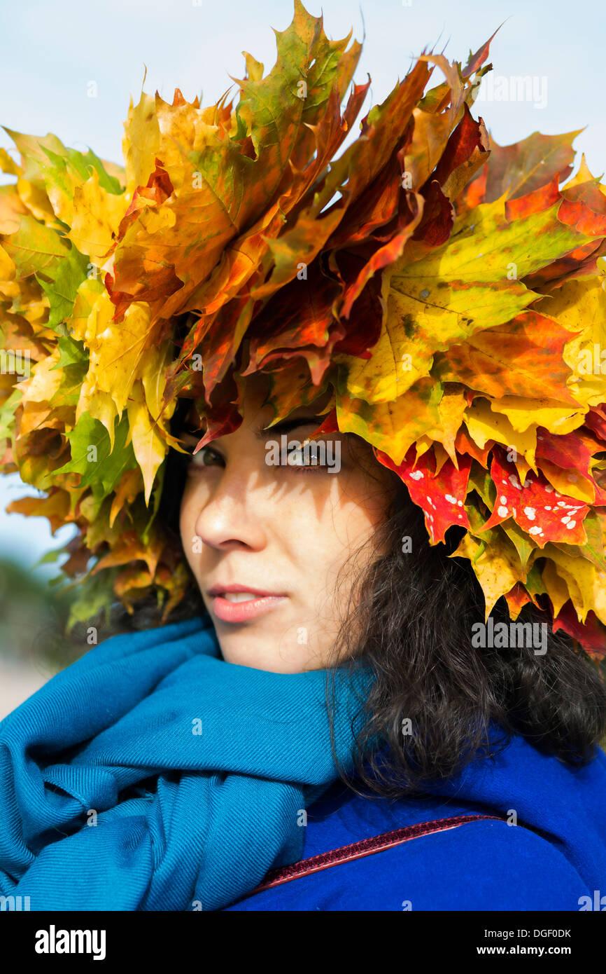 Frau mit Ahorn Blätter am Kopf Blick auf mysteriöse Weise Stockbild