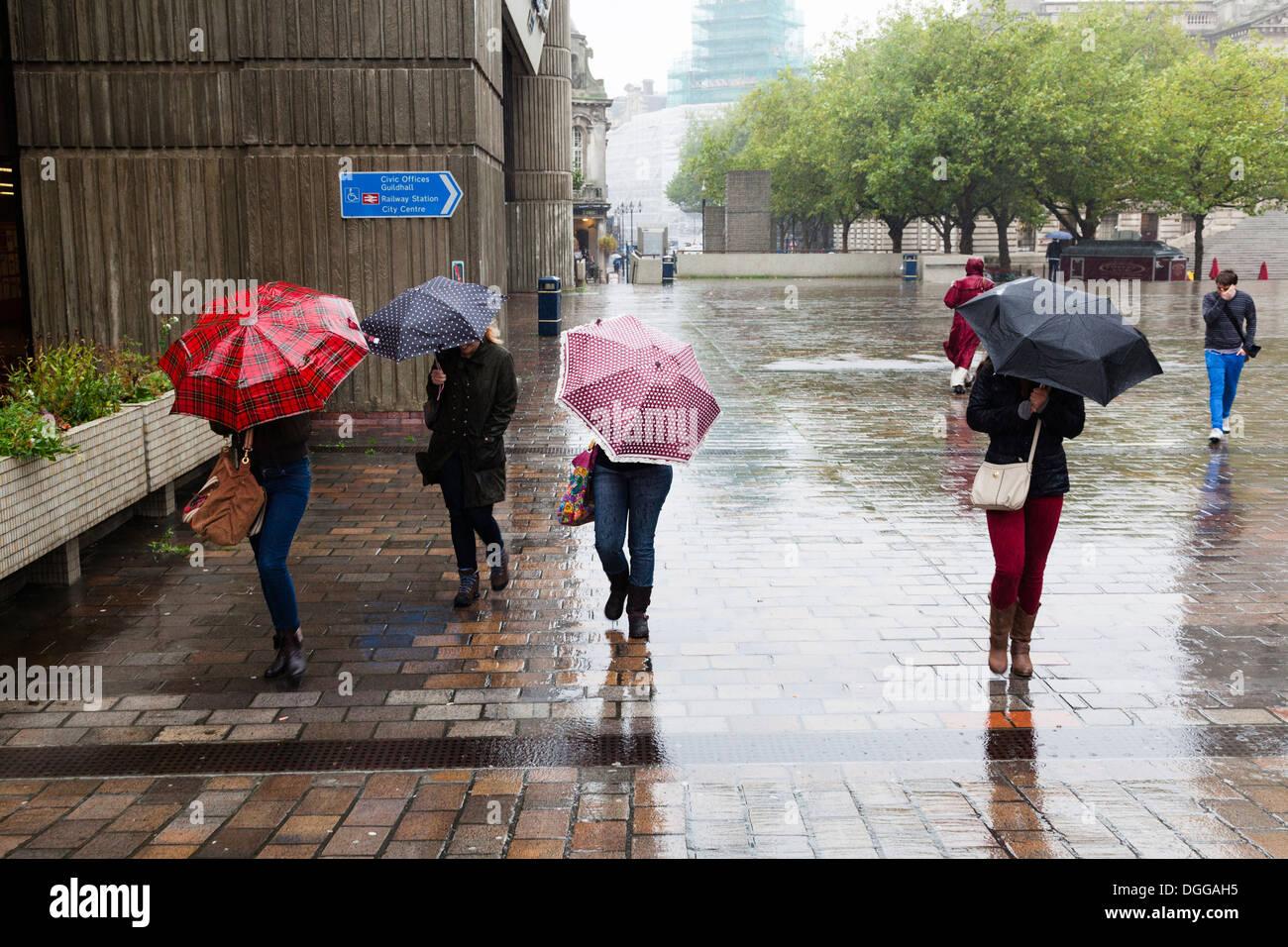 Vier Frauen mit Regenschirmen Kopf gegen Wind und Regen in der Stadt. Stockbild
