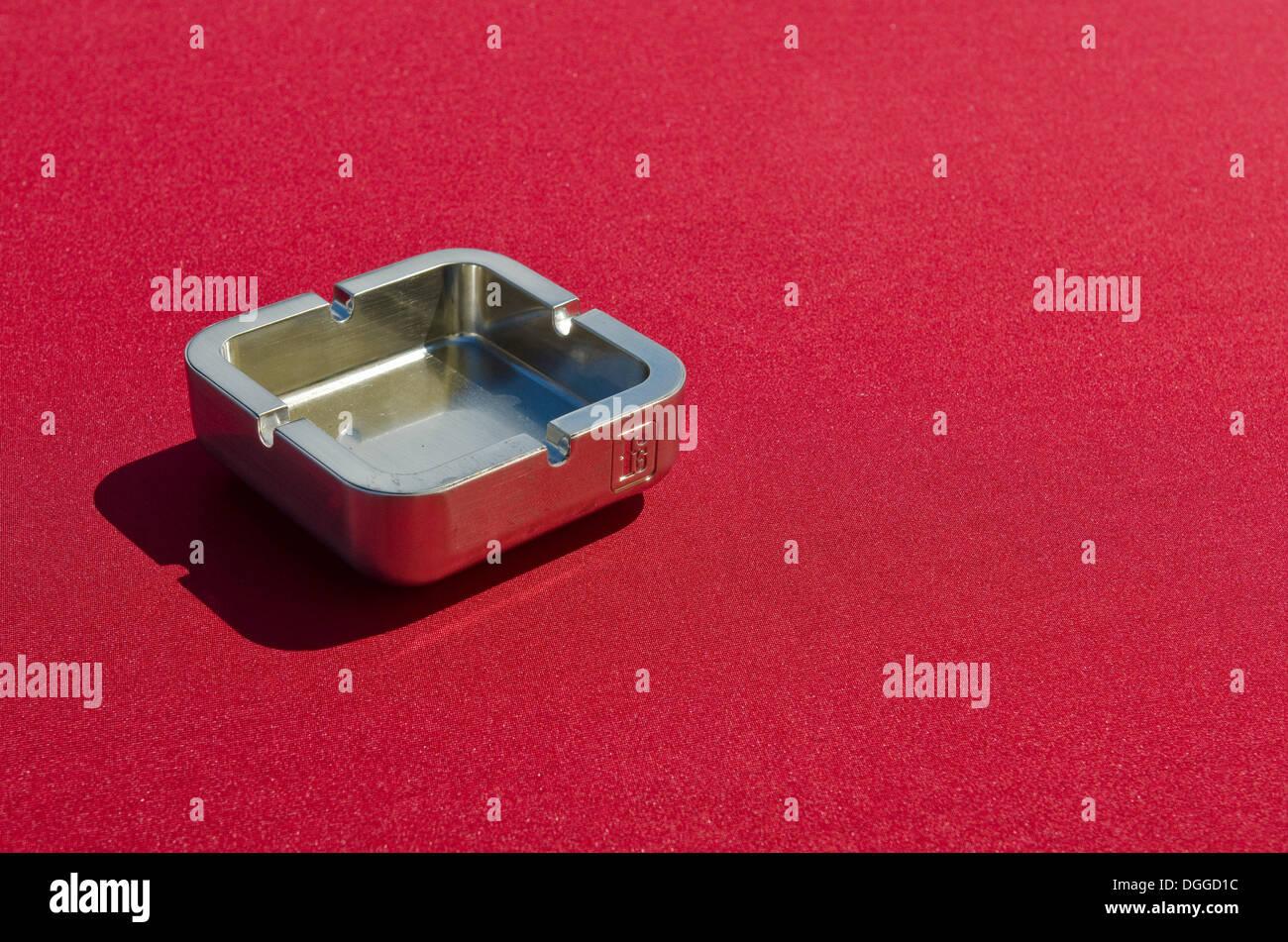 Metall Aschenbecher auf einer roten Tischdecke Stockbild
