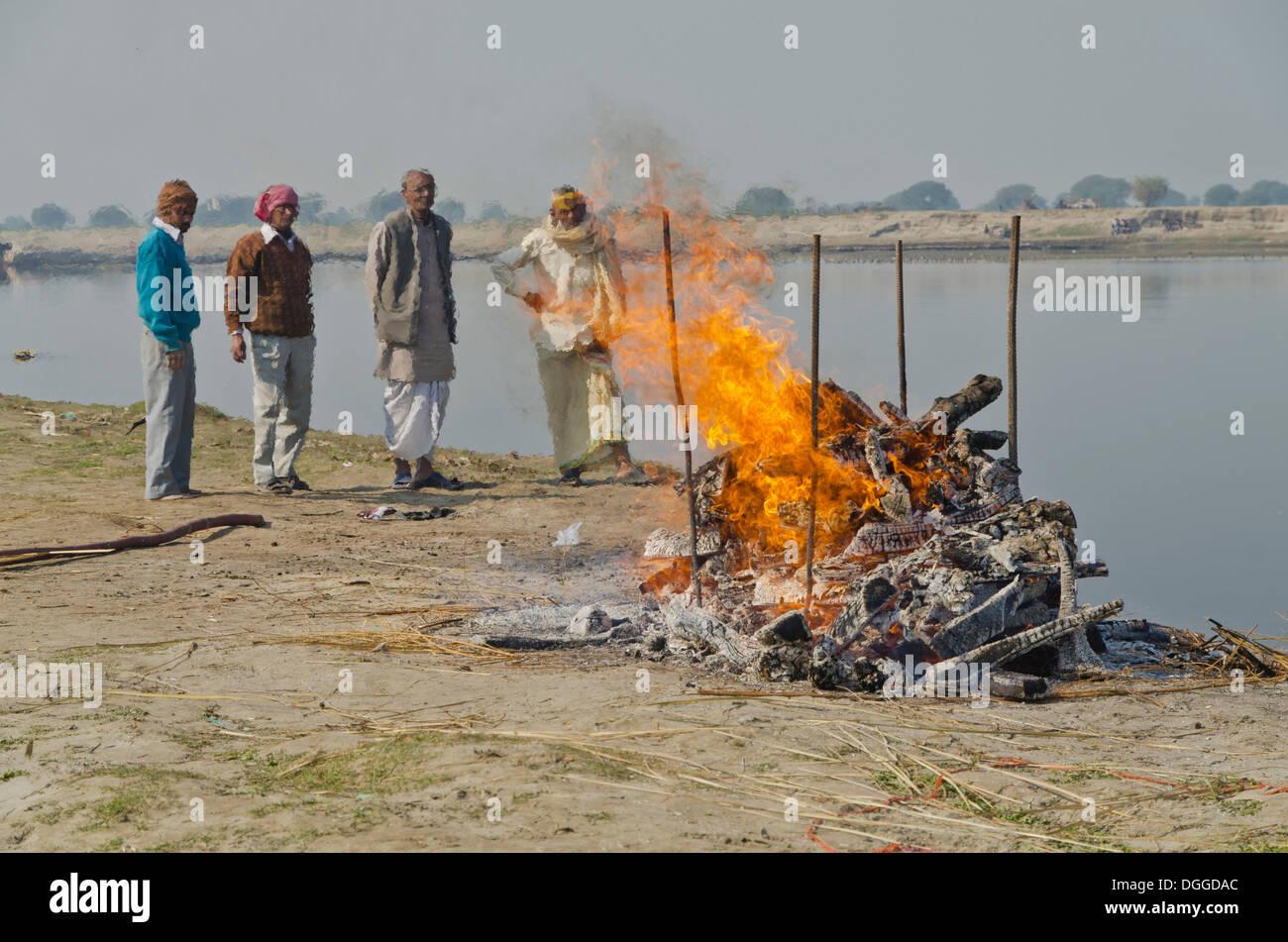 Gruppe von Menschen beobachten die Zeremonie Einäscherung eines Familienmitglieds am Ufer des Flusses Yamuna, Vrindavan, Stockfoto