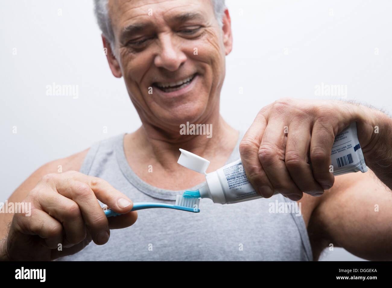 Ältere Mann drückte Zahnpasta auf die Bürste Stockfoto