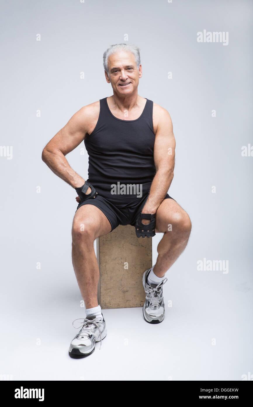 Senior woman in Sportbekleidung sitzt im Studio, Porträt Stockbild