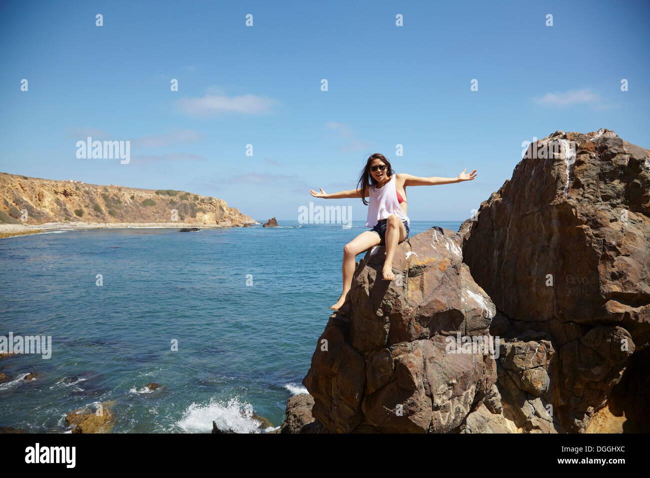 Junge Frau sitzt auf den Felsen, Palos Verdes, Kalifornien, USA Stockbild